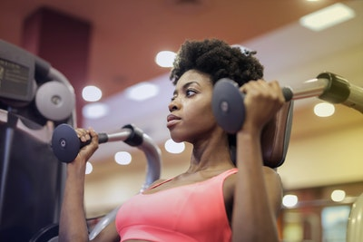 woman-in-pink-sport-bra-sitting-on-exercise-equipment-3775576
